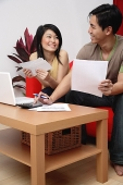 Couple in living room, doing finances - Asia Images Group