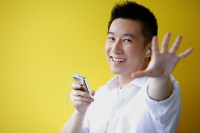 Man listening to MP3 Player, hand reaching towards camera - Asia Images Group