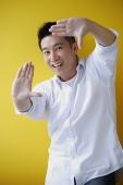 Man smiling at camera, making finger frame - Asia Images Group
