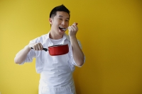 Man wearing apron and holding saucepan, eating from spoon - Asia Images Group