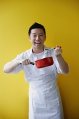 Man wearing apron and holding saucepan - Asia Images Group