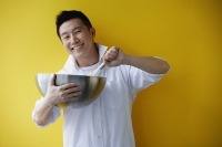 Man holding bowl and whisk - Asia Images Group