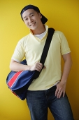 Man wearing cap and carrying satchel - Asia Images Group