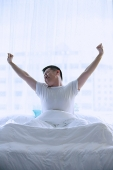 Man in bed, stretching - Asia Images Group