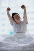Man sitting in bed, stretching - Asia Images Group