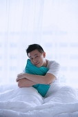 Man sitting in bed, embracing pillow, smiling at camera - Asia Images Group