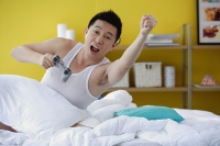 Man sitting in bed, holding video game remote control, arms outstretched - Asia Images Group