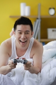 Man lying on bed, playing video game - Asia Images Group