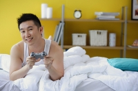 Man lying on bed, holding video game control - Asia Images Group