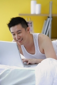 Man lying on bed using laptop - Asia Images Group