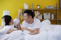 Couple lying on bed, smiling at each other - Asia Images Group