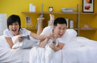 Couple lying on bed, playing video game - Asia Images Group