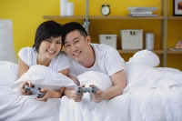 Couple lying on bed, holding video game controls, smiling at camera - Asia Images Group