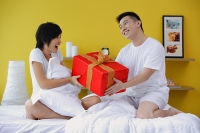 Couple sitting on bed, man giving woman present - Asia Images Group