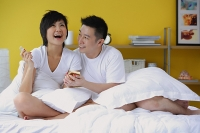 Couple in bedroom, woman opening present - Asia Images Group