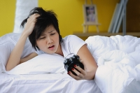 Woman in bed, looking at alarm clock - Asia Images Group