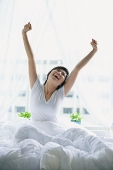 Woman in bed, stretching - Asia Images Group