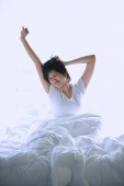 Woman stretching in bed - Asia Images Group