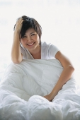 Woman sitting on bed, smiling at camera - Asia Images Group