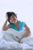 Woman sitting on bed, smiling, eyes closed - Asia Images Group