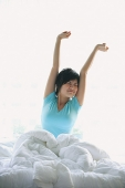 Woman stretching in bed, arms raised - Asia Images Group