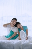 Couple sitting on bed, yawning - Asia Images Group