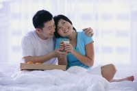 Couple sitting on bed, woman holding glass of milk - Asia Images Group