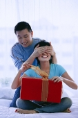 Couple in bedroom, woman opening gift, man covering her eyes - Asia Images Group