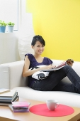Woman sitting on sofa, looking at camera - Asia Images Group