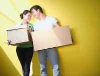 Couple carrying boxes, standing against yellow wall - Asia Images Group