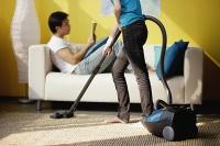 Woman vacuuming, man sitting on sofa reading magazine - Asia Images Group