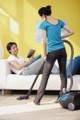 Woman vacuuming, man sitting on sofa with book, smiling at her - Asia Images Group