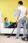 Man vacuuming, woman sitting on sofa with book, smiling at him - Asia Images Group