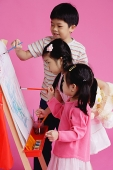 Three children painting on easel - Asia Images Group