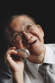 Senior man with mobile phone, looking up - Asia Images Group