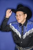 Senior man dressed in cowboy attire, adjusting hat - Asia Images Group