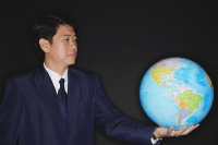 Businessman holding globe - Asia Images Group