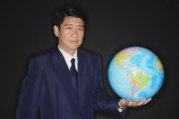 Businessman holding globe, looking at camera - Asia Images Group