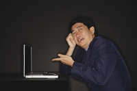 Businessman pointing at laptop next to him - Asia Images Group