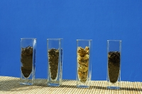Tea leaves in glass containers, in a row - Asia Images Group