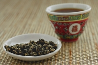 Tea leaves on plate with Chinese teacup - Asia Images Group