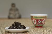 Chinese teacup and plate of tea leaves, still life - Asia Images Group