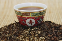 Chinese teacup and pile of loose tea leaves - Asia Images Group