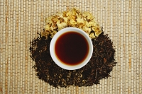 Chinese teacup and pile of loose tea leaves, directly above - Asia Images Group