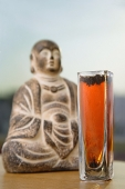 Glass with Tea next to Buddha icon, selective focus - Asia Images Group