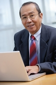 Businessman with laptop, smiling at camera - Asia Images Group