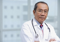 Doctor with arms crossed, looking at camera - Asia Images Group