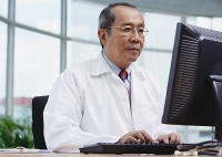 Doctor in office, using desktop computer - Asia Images Group