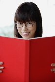 Young woman smiling at camera, holding book - Asia Images Group