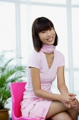Young woman dressed in pink, sitting on pink chair - Asia Images Group